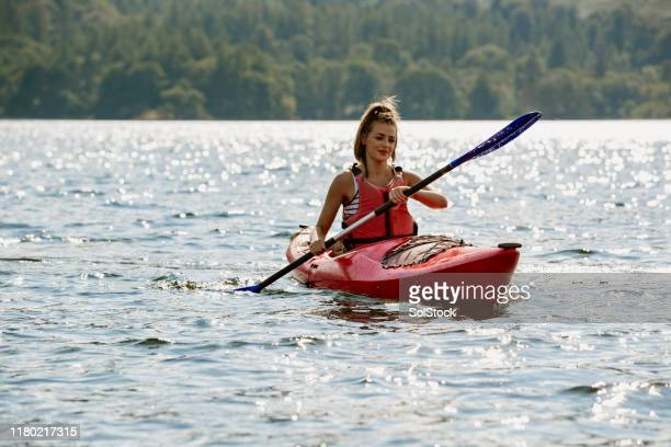 single female kayaking on lake - cumbria stock pictures, royalty-free photos & images