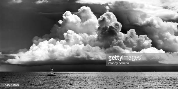 single fishing boat escaping from the storm - seascape stock pictures, royalty-free photos & images
