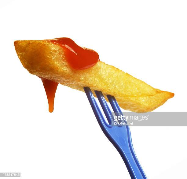 Single French fry on tiny blue prong smothered in ketchup