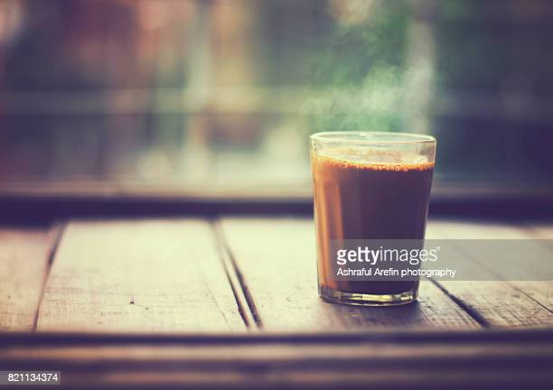 single glass of chai tea on table top - chai stock photos and pictures