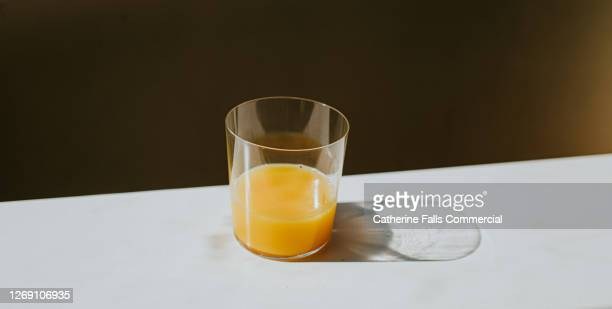 single glass of orange juice casting a shadow on a white surface with space for copy - orange stock pictures, royalty-free photos & images