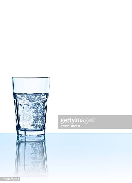 Single glass of sparkling water in blue, isolated on white