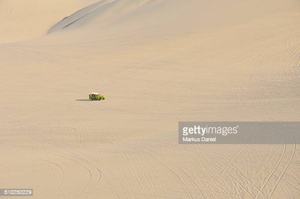 Single green dune buggy in the desert near Ica