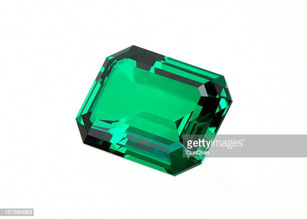 Single green emerald stone on a white background