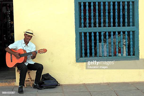 single guitar player plays music on colorful street in Trinidad Cuba