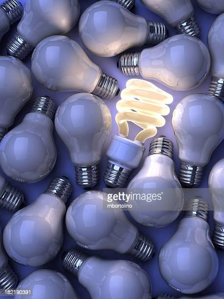 Single illuminated fluorescent lightbulb among plain bulbs