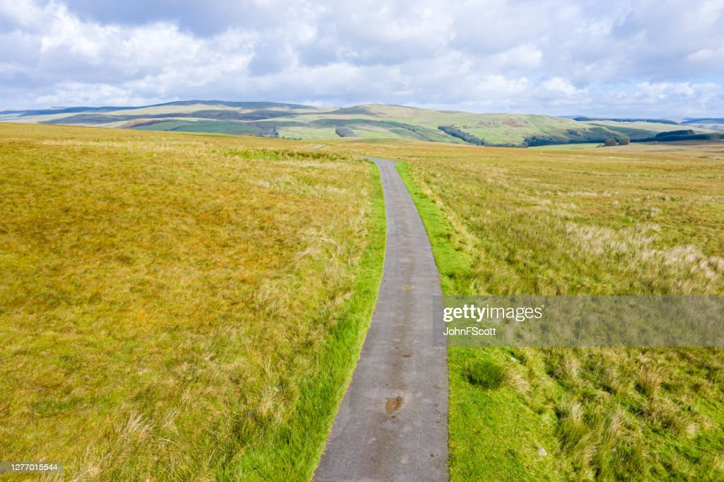 Single lane road running through remote open Scottish countryside as seen from a drone : Stock Photo