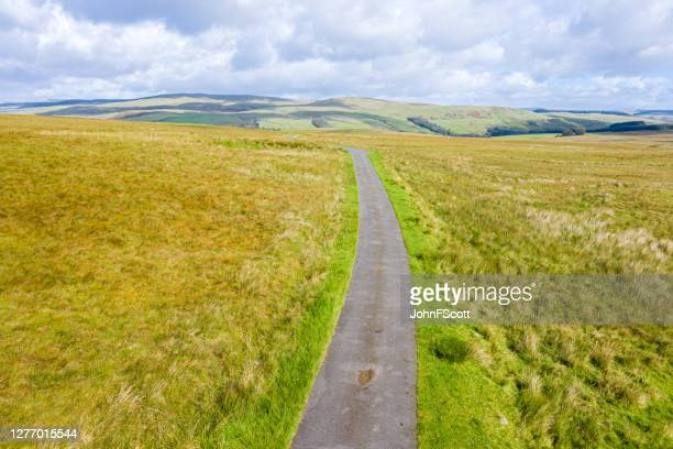 single lane road running through remote open scottish countryside as seen from a drone - johnfscott stock pictures, royalty-free photos & images