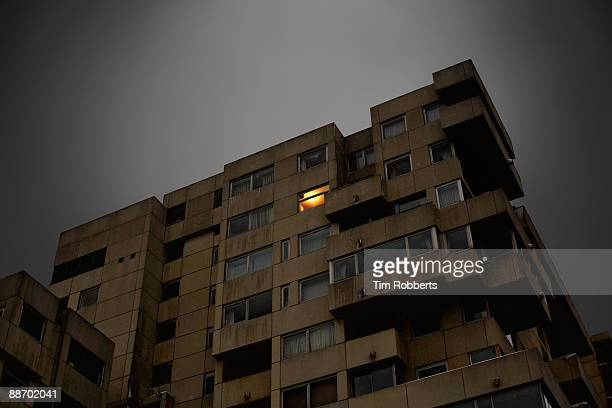 single light in window in apartment building - flat stock pictures, royalty-free photos & images