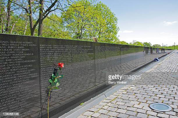 single long-stemmed red rose left atop names inscribed in vietnam veteran's memorial, washington dc, usa - vietnam veterans memorial stock photos and pictures