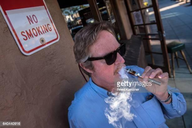 A single man smokes an electronic cigarette outside.