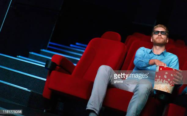 single man watching a movie. - action movie stock pictures, royalty-free photos & images