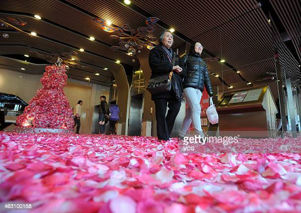 Single men and women toss peach petals to pray good luck for life and love on February 9 2015 in Wuhan Hubei province of China A hall at the first...