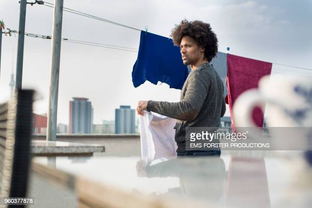single men is hanging out the laundry on his rooftop