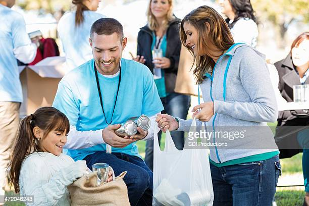 single mom and daughter accepting food donations from volunteer - donation box stock pictures, royalty-free photos & images