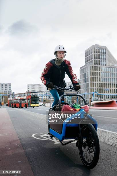 single mom cycling with child on cargo bike - helmet stock pictures, royalty-free photos & images