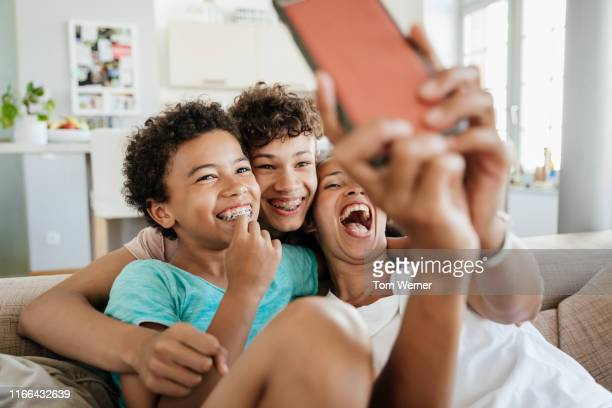 single mom having fun with her sons taking selfies - pre adolescent child stock pictures, royalty-free photos & images
