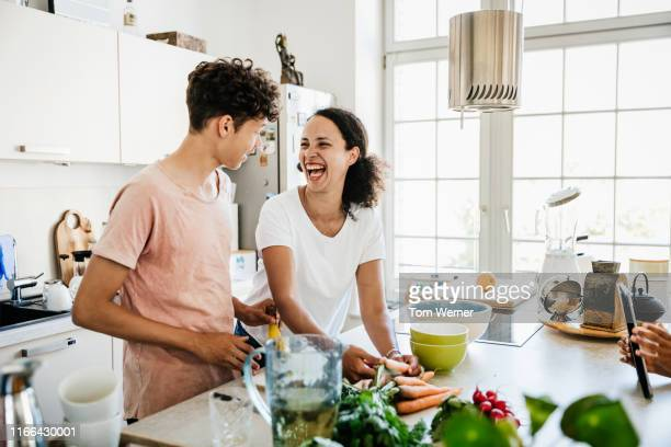 single mom laughing while preparing lunch with son - alimentação saudável imagens e fotografias de stock