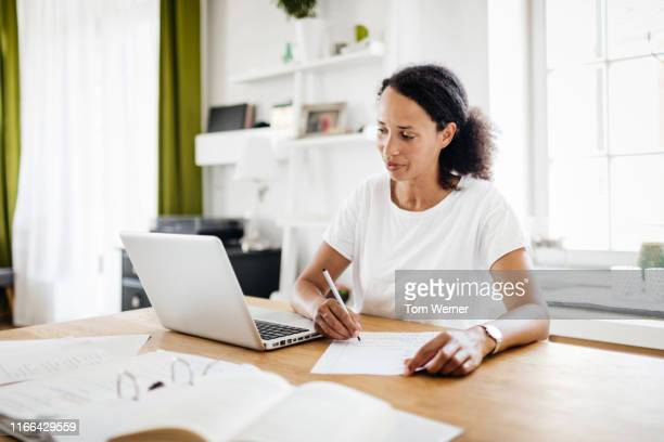 a single mom sitting at kitchen table working from home - ring binder stock pictures, royalty-free photos & images