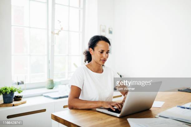 single mom working from home in her kitchen - working from home stock pictures, royalty-free photos & images