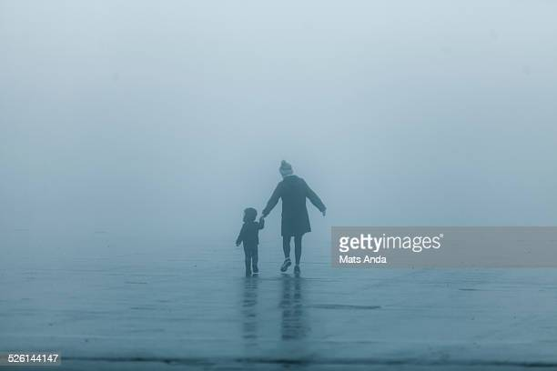 Single mother and child in abstract fog scene