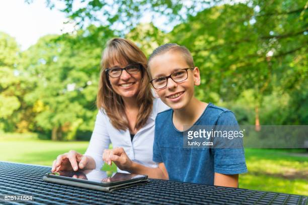 Single mother and teenage son using tablet