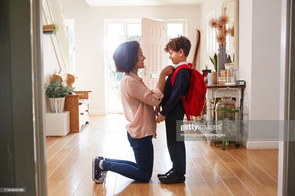 Single Mother At Home Getting Son Wearing Uniform Ready For First Day Of School : Stock Photo