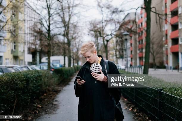 Single Mother Carrying Baby And Looking At Smartphone