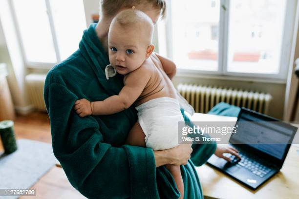 single mother checking emails while holding baby - bare breasted babes stock pictures, royalty-free photos & images
