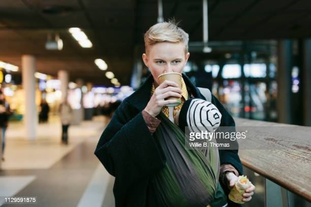 single mother drinking coffee while out with baby - on the move stock pictures, royalty-free photos & images