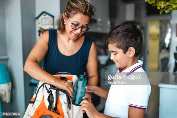 mãe solteira ajudando seu filho a se preparar para a escola - preparação - fotografias e filmes do acervo
