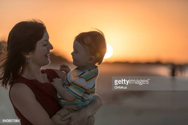 Single Mother Holding Baby Boy at Beach Sunset