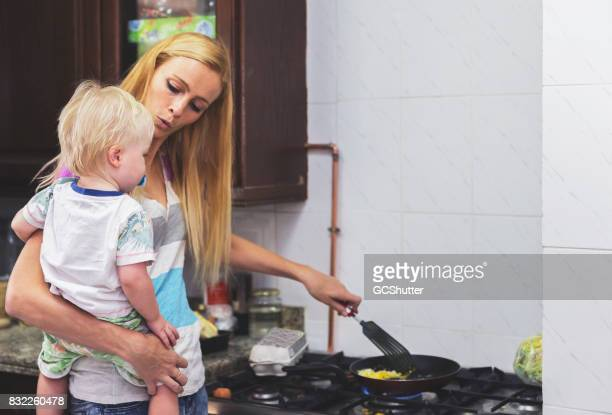 Single mother holding her child while cooking breakfast