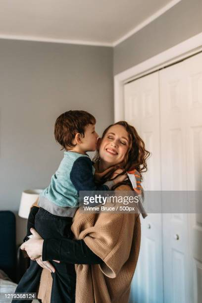 single mother holding her son - showus photos et images de collection