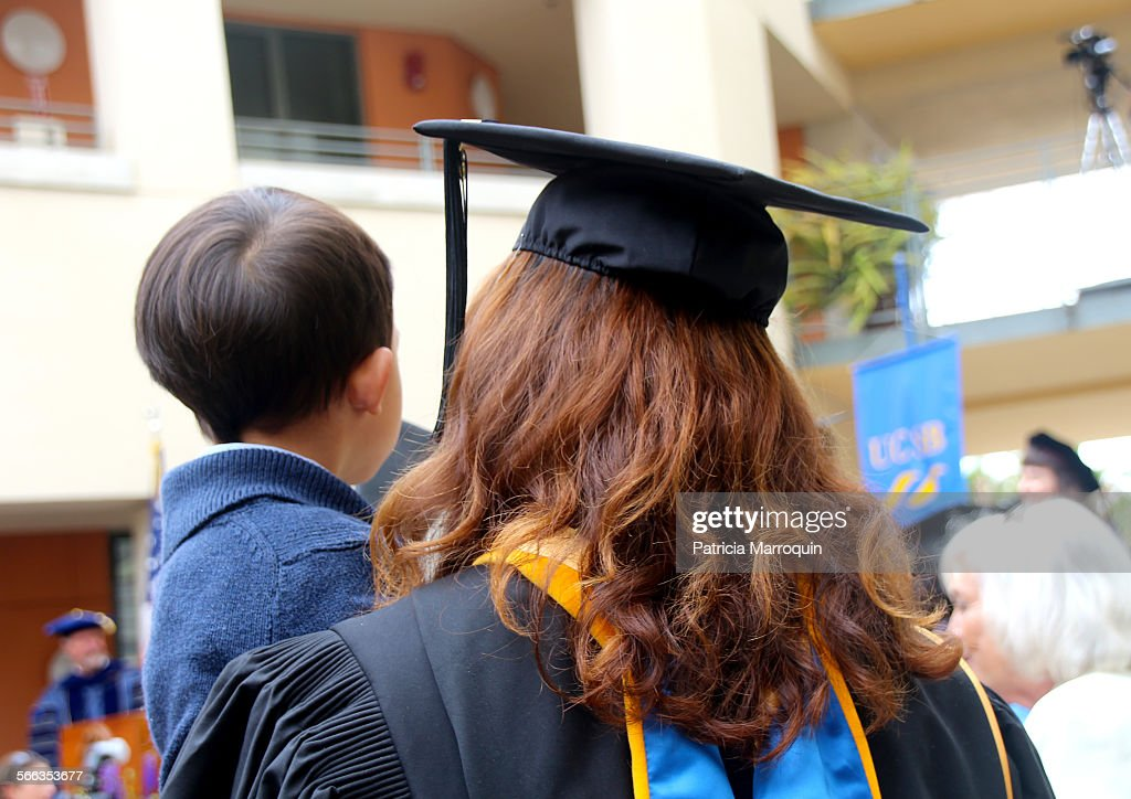 A single mother holds her son while she waits to receive her diploma during her graduation ceremony from college.