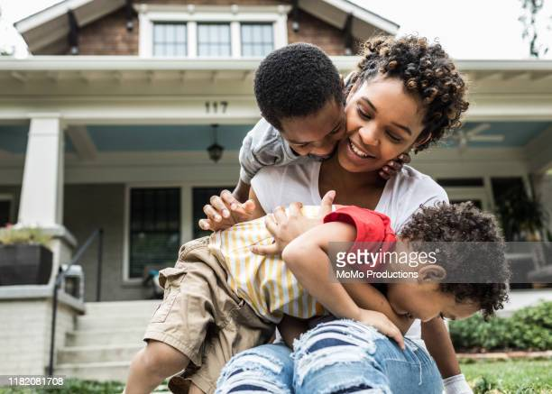 single mother playing with young sons in front of house - family stock pictures, royalty-free photos & images