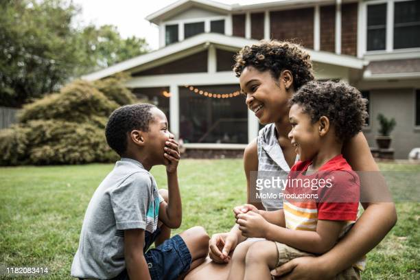 single mother playing with young sons in front of house - voor of achtertuin stockfoto's en -beelden