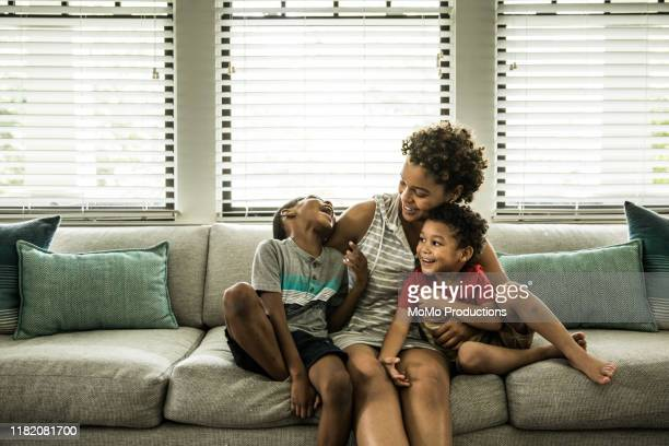 single mother playing with young sons on couch - single mother stock pictures, royalty-free photos & images