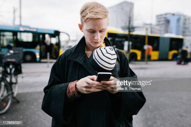 Single Mother Using Smartphone While Out With Baby