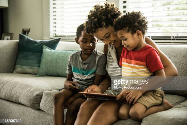 single mother using tablet with young sons on couch - family stock pictures, royalty-free photos & images