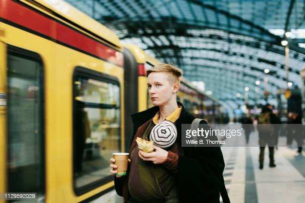 single mother waiting for train with baby - yellow coat stock pictures, royalty-free photos & images