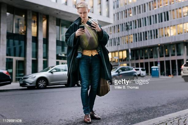 single mother walking with baby while using smartphone - leben in der stadt stock-fotos und bilder