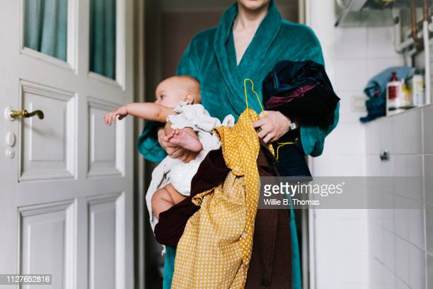 single mother with baby trying to get dressed - mother stock-fotos und bilder