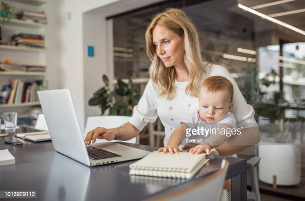 single mother with baby working in office - single mother stock photos and pictures