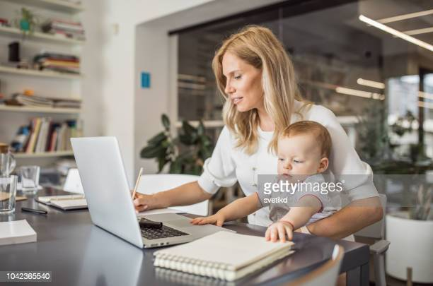 single mother with baby working in office - working mother stock pictures, royalty-free photos & images