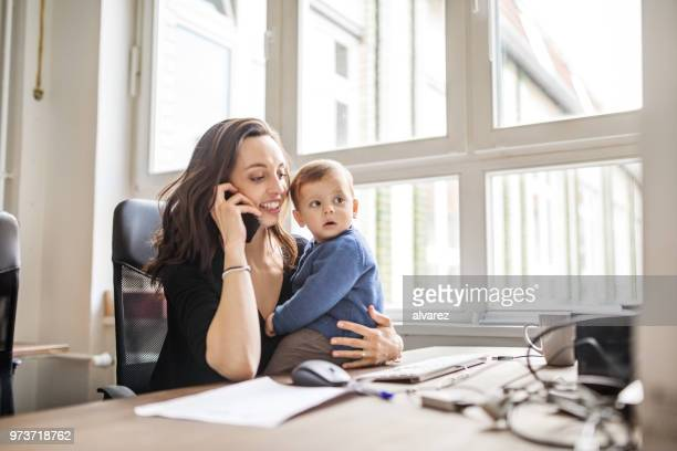 Single mother with son working in office