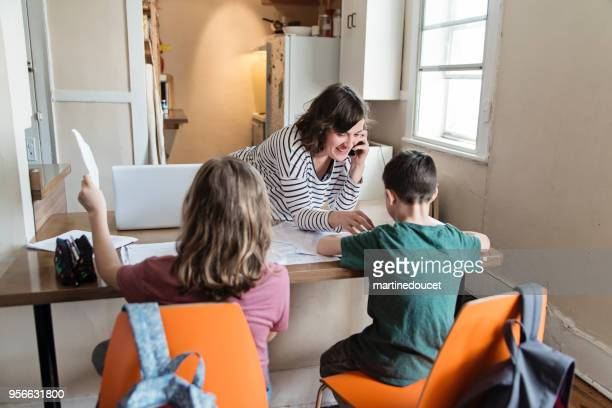 Single mother working from home with children.