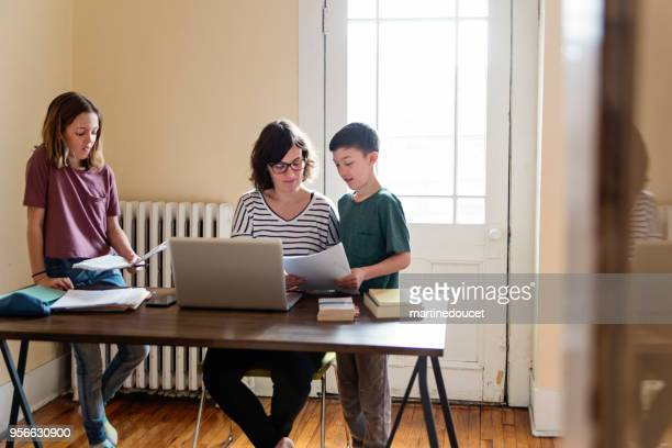Single mother working from home with preteen children.