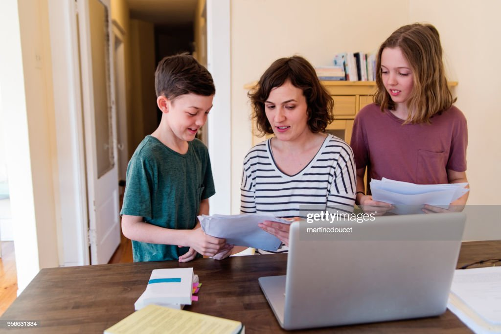 Single mother working from home with preteen children. : Stock Photo