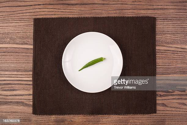 single okra on a plate on a wood table